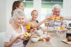 Happy multi-generation family eating fruits during breakfast Royalty Free Stock Image