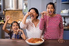 Happy multi-generation family eating spaghetti in kitchen Royalty Free Stock Image