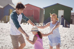 Happy multi-generation family holding hands at beach. During sunny day Stock Images