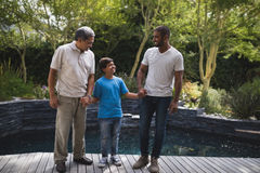 Happy multi-generation family holding hands at porch Stock Photos