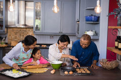 Happy multi-generation family preparing cookies in kitchen Royalty Free Stock Images