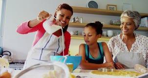 Happy multi-generation family preparing cookies in kitchen 4k. Happy multi-generation family preparing cookies in kitchen at home 4k stock footage