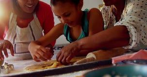 Happy multi-generation family preparing cookies in kitchen 4k. Happy multi-generation family preparing cookies in kitchen at home 4k stock video