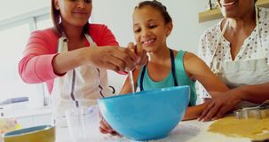 Happy multi-generation family preparing cookies in kitchen 4k. Happy multi-generation family preparing cookies in kitchen at home 4k stock video footage