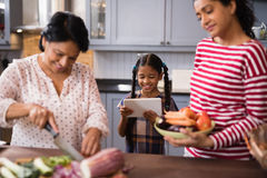 Happy multi-generation family preparing food in kitchen Stock Images