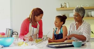 Happy multi-generation family preparing gingerbread in kitchen 4k. Happy multi-generation family preparing gingerbread in kitchen at home 4k stock video footage