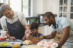 Happy multi-generation family preparing sweet food together in kitchen Royalty Free Stock Image