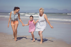 Happy multi-generation family running while holding hands at beach. During sunny day Stock Images