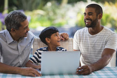 Happy multi-generation family sitting by laptop at porch Stock Photography
