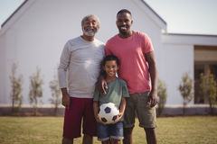 Happy multi-generation family standing in garden with football Royalty Free Stock Photos
