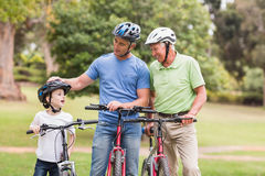 Happy multi generation family on their bike at the park Royalty Free Stock Photos