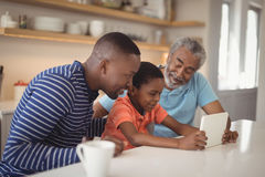 Happy multi-generation family using digital tablet in kitchen stock image