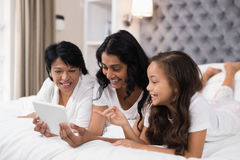 Happy multi-generation family using digital tablet while lying on bed Stock Photo