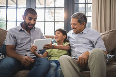 Happy multi-generation family using digital tablet together at home Royalty Free Stock Image