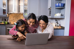 Happy multi-generation family using laptop in kitchen Stock Photos