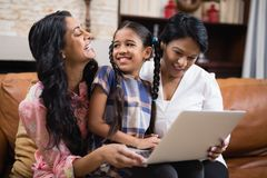 Happy multi-generation family using laptop while sitting together. On sofa at home Royalty Free Stock Photo