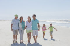 Happy multi-generation family walking on sunny beach Royalty Free Stock Photo