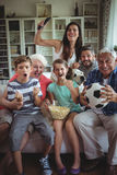 Happy multi-generation family watching soccer match on television in living room Royalty Free Stock Image