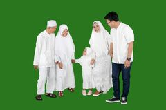 Happy multi-generation muslim family standing while chatting in studio