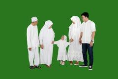 Happy multi-generation muslim family standing in studio