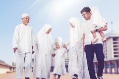 Happy multi-generation muslim family walk together outdoor