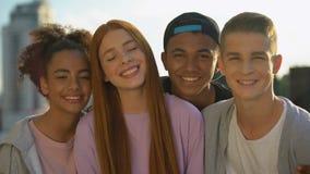 Happy multi-racial friends smiling camera, teenage unity, cheerful millennial