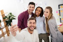 Happy multicultural business people taking selfie on smartphone together. In office stock photo