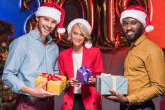 Happy multicultural businesspeople in santa hats holding presents at new year. Corporate party royalty free stock images