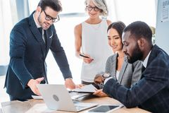 Happy multicultural businesspeople working on project in office and looking. At laptop royalty free stock photos