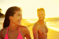 Happy multicultural couple on beach vacations. Hawaii holidays in sunset, young healthy adults together laughing walking in summer day. Asian mixed race woman royalty free stock photo