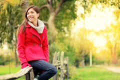 Happy multicultural fall woman. Happy fall woman sitting on countryside fence smiling joyful in autumn forest. Young beautiful multicultural Caucasian / Asian Stock Photography