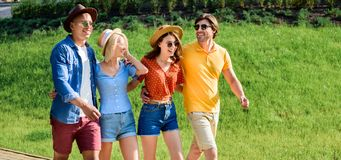 Happy multicultural group of friends walking on street together. On summer day royalty free stock image