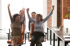 Happy multicultural office workers laughing having fun riding on chairs. Happy multicultural office workers people group laughing having fun riding on chairs stock images