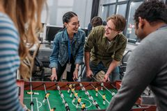 Happy multicultural people playing in table soccer. At modern office stock photos