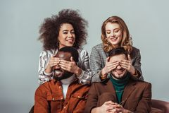 happy multicultural retro styled girls covering eyes to multiethnic men stock photography