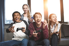 Happy multicultural teenagers playing video games with joysticks at home Stock Photos