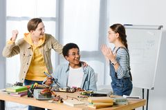 Happy multicultural teenagers showing yes gesture while engineering. At home stock photography