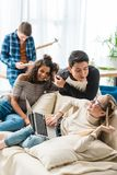 Happy multicultural teenagers talking and using. Laptop royalty free stock images