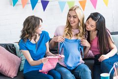 Happy multicultural women choosing baby clothes with pregnant friend. Baby-party concept stock photography