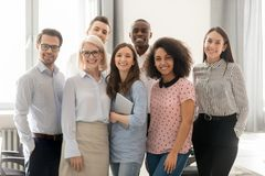 Happy multicultural work team looking at camera posing in office stock images