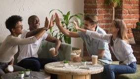 Happy multicultural friends  group giving high five at coffeehouse meeting royalty free stock photography