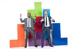 happy multiethnic businessmen standing near colorful blocks royalty free stock image