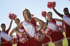 Happy Multiethnic Cheerleaders. Portrait of multiethnic cheerleaders with pom-pom on field Stock Images