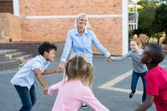 Children and teacher playing together. Happy multiethnic children having fun and playing ring around the rosie with teacher. School kids playing the game in royalty free stock photo