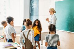 Happy multiethnic classmates standing around teacher. At classroom stock photos