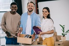 Happy multiethnic colleagues with cardboard box and office supplies smiling at camera. In new office stock photography