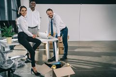 Happy multiethnic colleagues smiling at camera while moving. In new office royalty free stock image