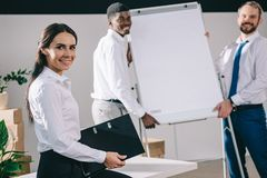 Happy multiethnic colleagues smiling at camera while relocating. In new office royalty free stock photo