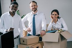 Happy multiethnic colleagues smiling at camera while unpacking cardboard boxes in new office royalty free stock photos