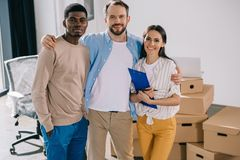 Happy multiethnic colleagues standing together and smiling at camera. In new office stock photos